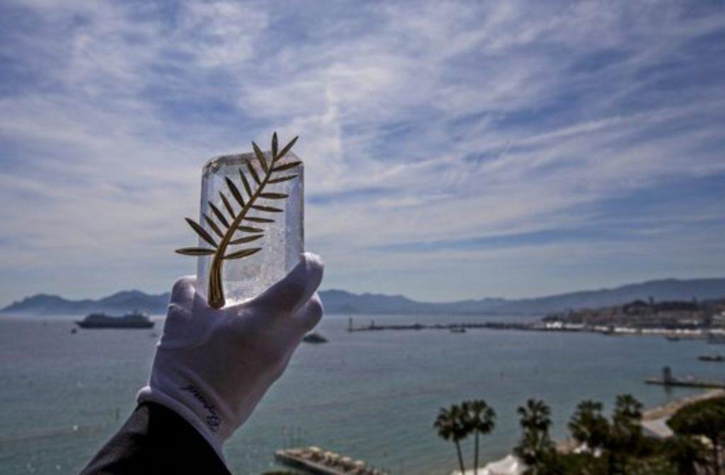 La palma d'oro viene sollevata da una mano con un guanto bianco. Sullo sfondo, il mare di Cannes