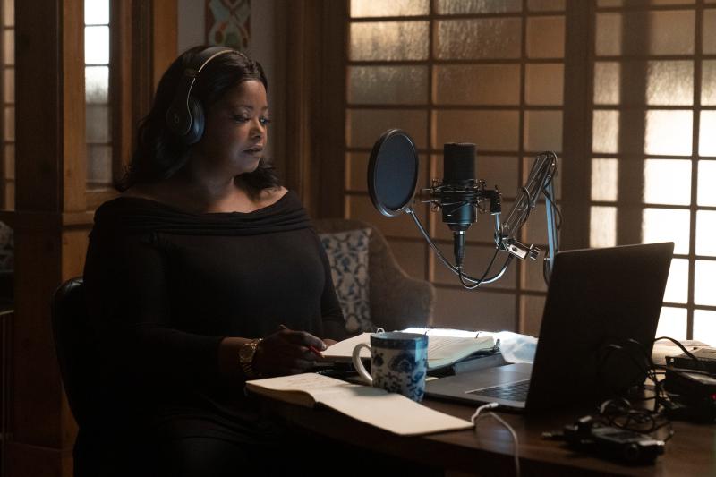 Poppy è seduta a un tavolo e indossa delle cuffie. Davanti a lei, un microfono, un computer e dei quaderni di appunti.