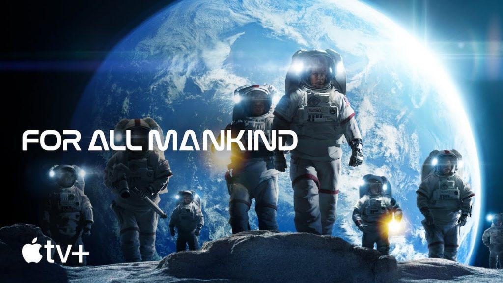 Alcuni astronauti sul suolo lunare. Sullo sfondo, la Terra, immensa e sferica, immersa nell'oscurità dello spazio.